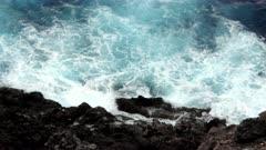 Waves crashing along a volcanic cliff