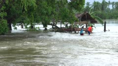 People Wade Through Dangerous Fast Flowing Flood Waters