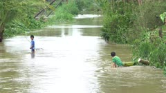 Children Play In Dirty Flood Waters After Tropical Storm Hits