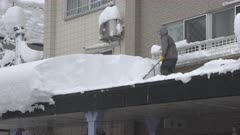 Man Shovels Deep Snow From Roof Top After Winter Storm