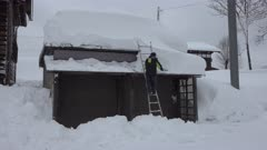 Man Clears Huge Snow Fall From Roof Of House After Blizzard