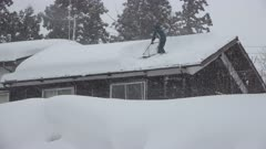 Man Shovels Deep Snow Off Roof During Blizzard