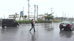Man Carries Child In Strong Hurricane Wind