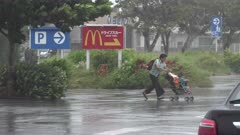 Woman Pushes Baby Stroller In Hurricane Wind And Rain