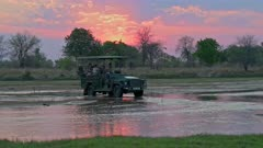 Tourists in safari vehicle crossing the Kapamba River with sunset behind, South Luangwa National Park, Mfuwe, Zambia, Africa
