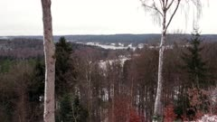 Top of a hill view of forest and a lake in the winter.