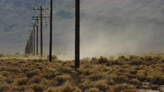 Dust Devil, Whirlwind, Desert Tornado Roars a Row of Power Poles in the Mojave Desert