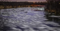 Des Moines river freezing over at night under the starlight.  Trains pass by over a bridge in background. A hypnotic midwestern oddity.