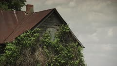 Old Decrepit Farm House sits long forgotten in an empty field on a perfect mid-summers day in Iowa