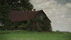 Old Farmhouse rests in abandonment in a empty field on a hot summers day in Iowa