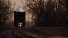 Freight Train Leaving Industrial Coal Firing Plant with Distant Steam Stack creates an Optical Illusion as it crosses a early 20th Century Iron Truss Bridge