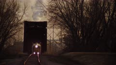 Freight Train Leaving Industrial Coal Firing Plant crosses an early 20th Iron Truss Bridge, creating an Optical Illusion with the Distant Steam Stack in the Distance