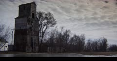Abandoned midwestern Grain Mill with late winter gloom and barren trees