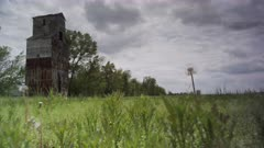 Abandoned Grain Mill in a pastoral prairie bathed with sunshine and springtime developing storms