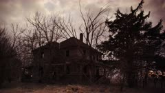 Spooky abandoned Victorian  farm house surrounded by unkept trees under a dreary fall sky.