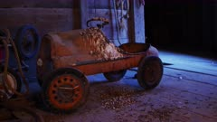 Vintage toy pedal car, covered with pigeon droppings, rests forgotten and neglected in an old hay barn in Iowa