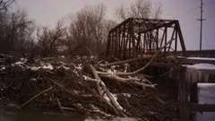 Old iron truss bridge clogged with dead trees, logs and debris on the Des Moines River in the dead of late winter Iowa.