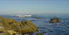 Ocean scenic, waves break over nearshore rocks, jib arm shot