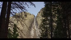 Yosemite Falls with low water flow between conifer trees, winter