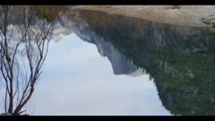 Reflective mountain top in slow moving river, Half Dome