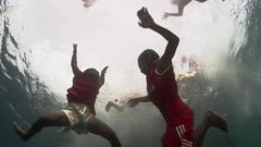 Indonesian Children jumping into the water from a dock