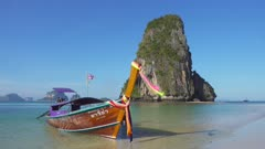 Long tail boat on tropical beach (Pranang beach) and rock, Krabi, Thailand, 4k