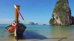 Long tail boat on tropical beach (Pranang beach) and rock, Krabi, Thailand, 4k