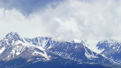 snow-capped mountain peaks among the clouds, timelapse