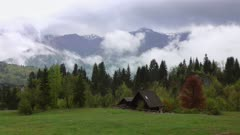 Mountain alps landscape with house and trees in fog clouds in Slovenia at spring, 4k