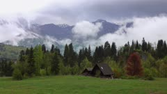 Mountain alps landscape with house and trees in fog clouds in Slovenia at spring, timelapse, 4k