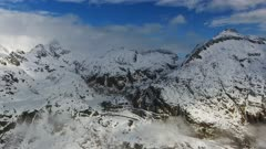 Flying over snow-capped mountains in clouds. Aerial landscape in Adamello Brenta, Italy, 4k