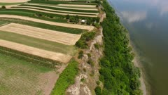 Aerial view of colorful fields on high bank of Danube river in Serbia, tilt view 4k