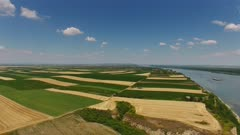 Aerial view of colorful fields on high bank of Danube river in Serbia, panorama 4k