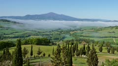 Fog over farmland hill country in Tuscany, Italy, panorama timelapse