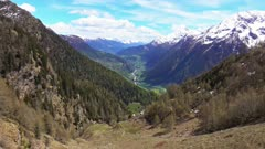 Beautiful top view of high snow-covered mountains and valley with road and village in Switzerland, tilt view 4k