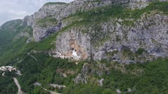 Aerial panorama with Ostrog Monastery church under tall mountain walls, Montenegro, 4k