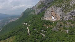 Aerial view on Ostrog Monastery church under tall mountain walls, Montenegro, 4k