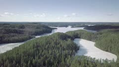 Aerial landscape of rocky natural boreal forests and frozen lakes during spring in Kolovesi national park, Finland.