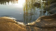 Glimmering sunlight reflecting from water surface at rocky lake shore.