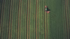 Farming and ploughing fields in spring with tractor. Top down aerial drone view