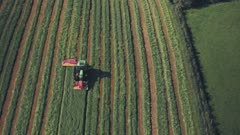 Harvesting crops on a farm with a tractor. Aerial drone view