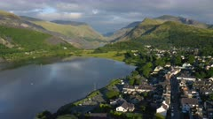 Sprawling Lush Green Landscape And A Provincial Village in Snowdonia Wales UK - aerial shot