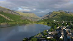 Idyllic, picturesque Llanberis town in Wales, with mountains landscape and forest scenery beside Padarn Lake, aerial drone view moving backwards