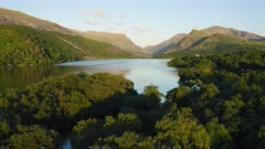 Beautiful landscape of Llyn Padarn Lake surrounded by lush forest and mountains in Snowdonia National Park, Wales
