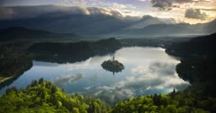 Timelapse of mountain landscape at sunrise with sunlight hitting Lake Bled island in Slovenia. Time lapse of clouds forming over Julian Alps Mountains Range