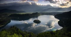 Lake Bled island landscape timelapse in Slovenia. Time lapse of clouds over Julian Alps Mountains Range with beautiful morning light hitting the church, castle and landscape