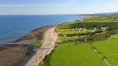 Aerial drone shot of Idyllic green farmland and fields on coast of Wales on sunny summer day with low tide ocean and beach