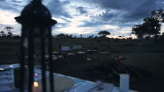A luxury glamping camping safari dinner table Set Up with a fire at a Lodge accommodation In Kenya -wide shot