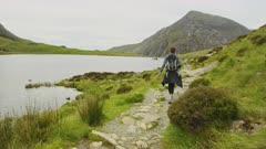 Woman hiking along idyllic shore of Llyn Idwal lake in mountains of Snowdonia