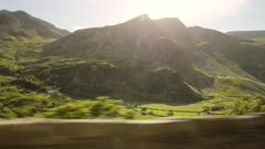 Scenic Drive Through The Lush Green Mountain Terrain During Sunset In Snowdonia National Park In Wales - Wide Shot
